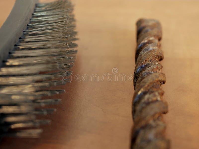 Borsta på metall och den rostiga drillborren mot tabellen fotografering för bildbyråer