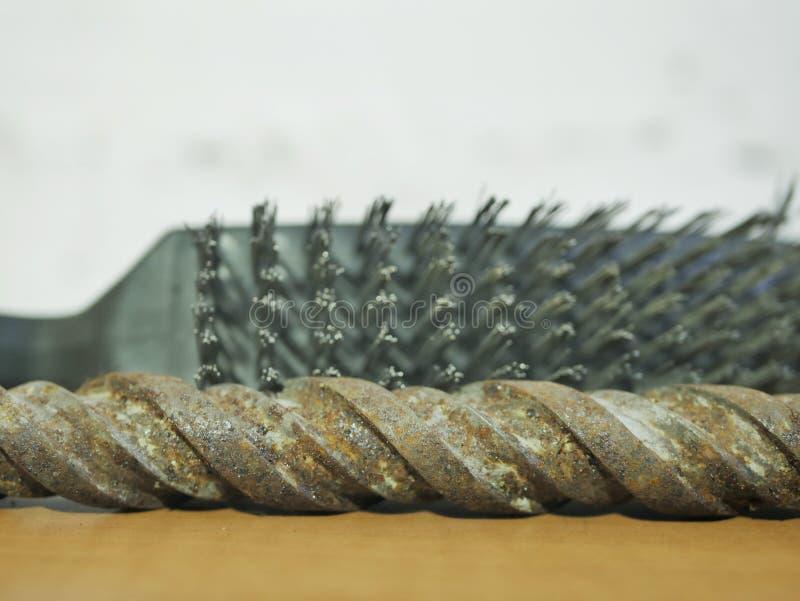 Borsta på metall och den rostiga drillborren mot väggen royaltyfri foto