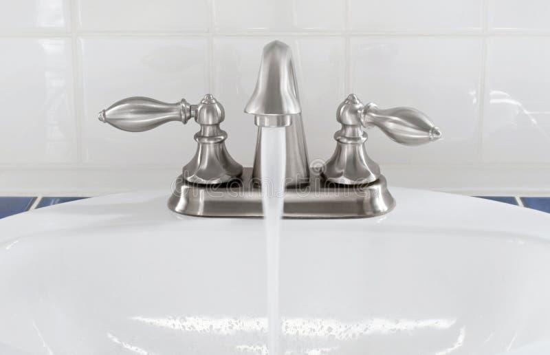 Borstad myntvattenkran med rinnande vatten arkivbild