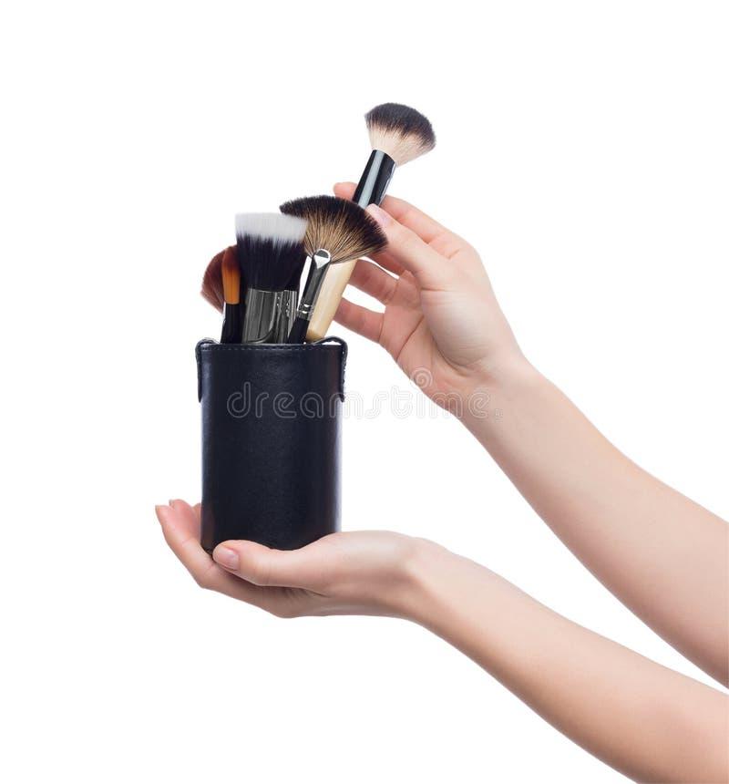 Borstar det hållande yrkesmässiga sminket för kvinnan i kosmetisk påse royaltyfri foto