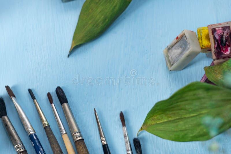 Borstar, vattenfärgmålarfärger, gröna dekorativa sidor och ett ark av papper på en blå bakgrund placera text Top besk?dar arkivbild