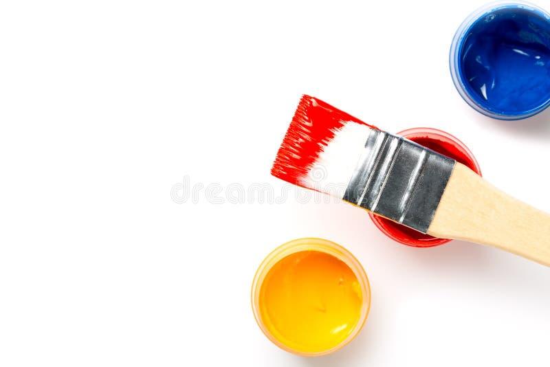 Borstel en kleurrijke die flessen met verf op witte achtergrond wordt geïsoleerd Hoogste mening stock afbeelding