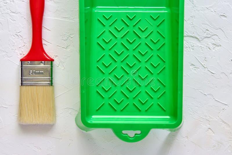 Borstel met rood handvat en groen verfdienblad op witte concrete achtergrond Hulpmiddelen en toebehoren voor huisvernieuwing Hoog royalty-vrije stock fotografie