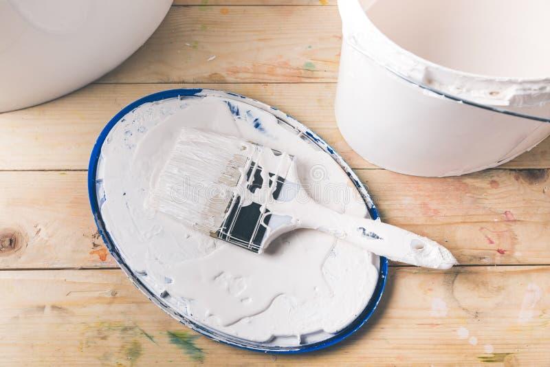 Borstel in witte verf op dekking stock foto
