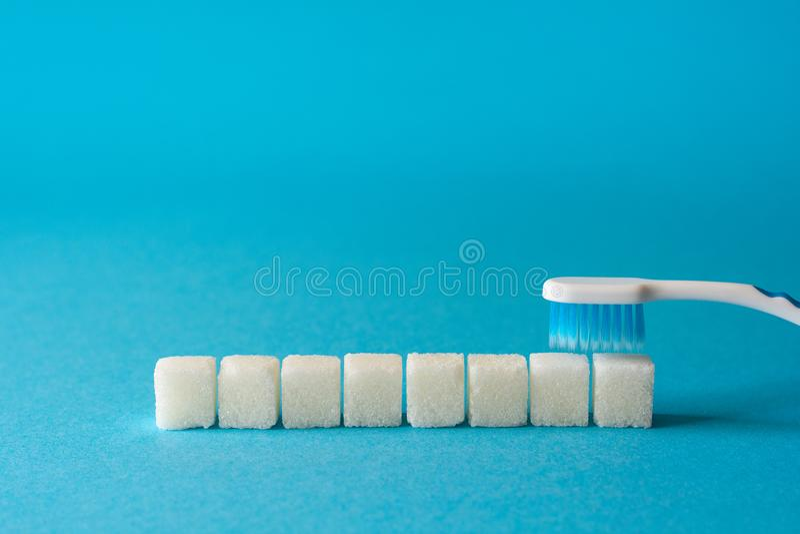 Borstelende Tanden De tandenborstel maakt vuil van tanden schoon Van suikerkubussen en sesamzaden allegorie Geïsoleerd over witte stock afbeeldingen