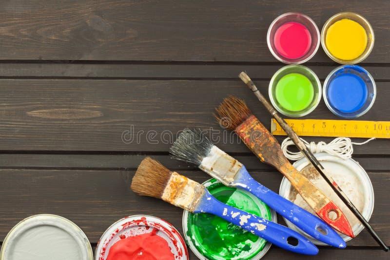 Borstels en verf op een houten lijst Schildershulpmiddelen Workshopschilder Behoeften het schilderen Verkoop die behoeften schild stock foto