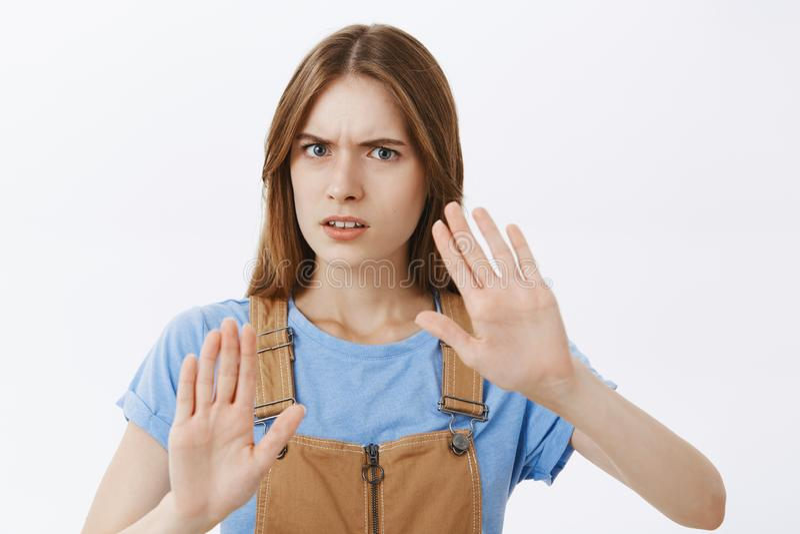 bort mig stay Ståenden av bekymrat missnöjt och allvarligt lyfta för ung kvinna gömma i handflatan, i att rynka pannan för skydds royaltyfria foton