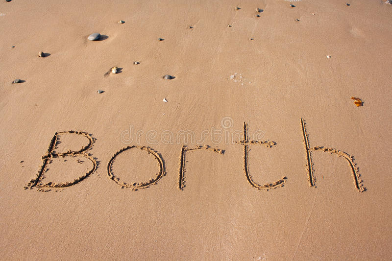 Borth on sand. Borth written onto a sandy beach with the sea swashing across it stock images