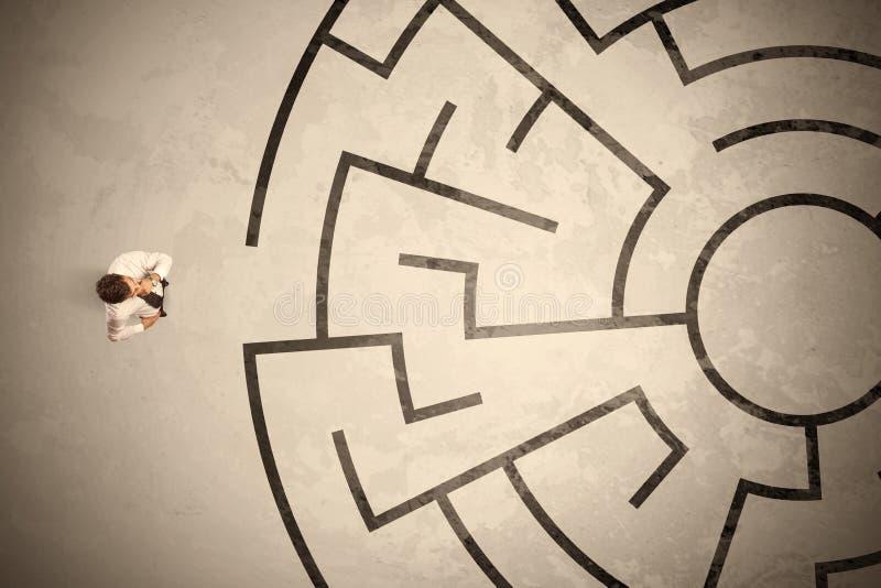 Borttappad affärsman som söker efter en väg i rund labyrint arkivbild