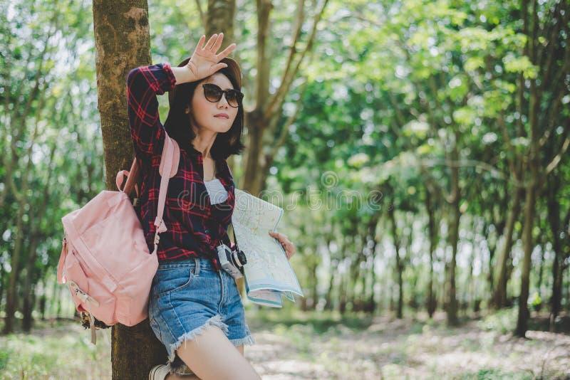 Borttappad asiatisk kvinnlig handelsresande trötta från hennes väg i skogkvinnan som bort torkar svett vid handen Solo flickaresa royaltyfria foton