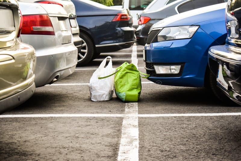 Borttappade bagages i parkeringen till och med bilarna Forgoten påsar på stadsparkeringen royaltyfri foto