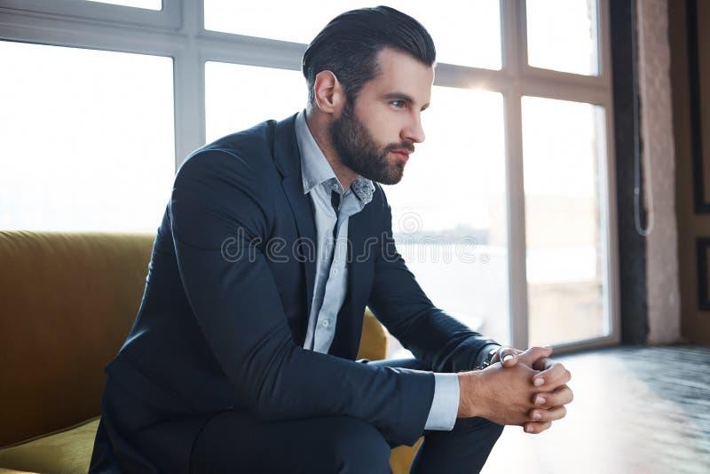 Borttappat i affärstankar Den fundersamma stiliga unga affärsmannen tänker om affär, medan sitta på soffan arkivfoton