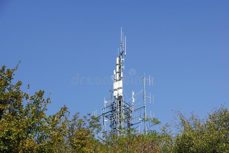 Bos van antennes op toren bovenop heuvel stock foto's