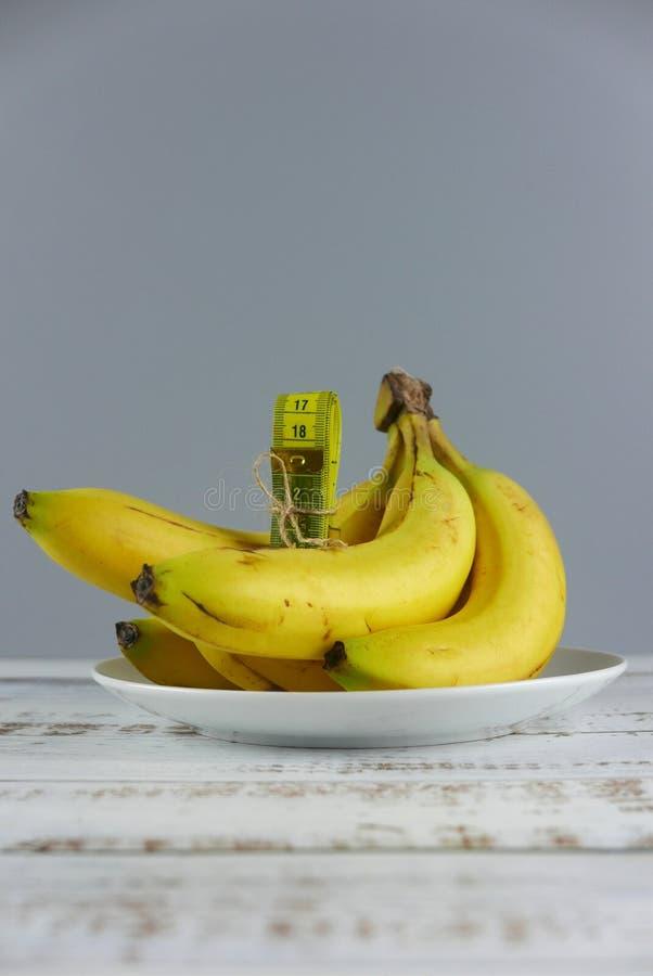 Bos van bananen en het meten van band op houten achtergrond Verticaal schot Exemplaarruimte voor tekst of embleem stock foto