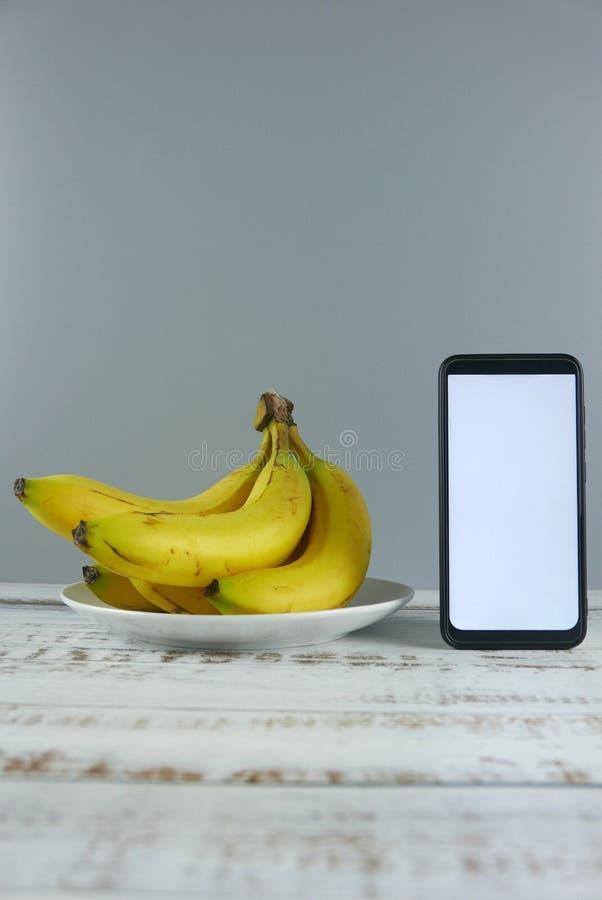 Bos van bananen en smartphone op houten achtergrond Model voor het gezond eten, dieet, mobiele telefoontoepassing, de dienst, en royalty-vrije stock afbeeldingen