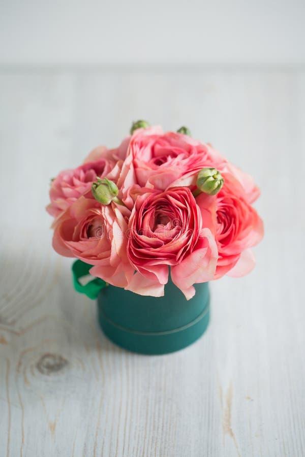 Bos van bleek - roze ranunculus Perzische boterbloemen lichte achtergrond, houten oppervlakte Groene doos stock afbeelding
