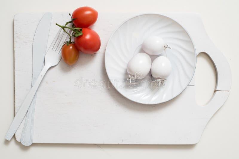 Bos van de beelden van de tomatenvoorraad De witte plaat van het vorkmes op een oud houten plankdienblad De witte die tomaten van royalty-vrije stock fotografie