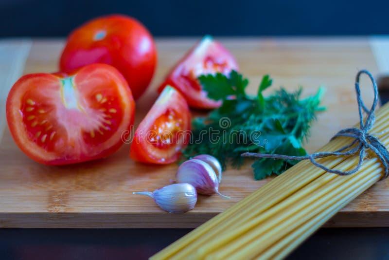 Bos van de ongekookte gehele deegwaren van de tarwespaghetti met tomaten, garlik en greens stock foto