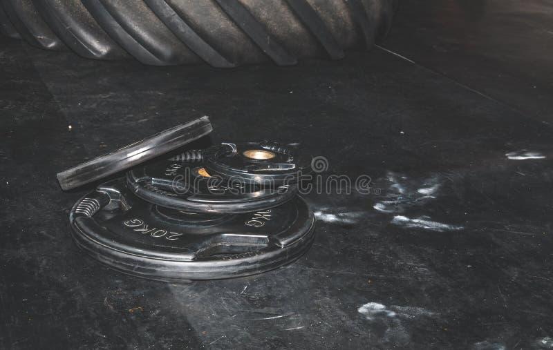 Bos van de zware zwarte die platen van het barbellgewicht op de gymnastiekvloer op het harde van het de training sterke contrast  royalty-vrije stock foto's