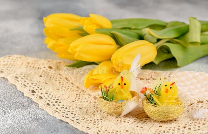 Bos van geel tulpen en kip-speelgoed op een lichte achtergrond royalty-vrije stock afbeeldingen