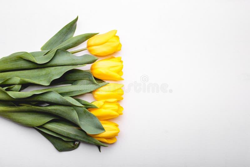 Bos van gele tulpen op witte houten achtergrond stock afbeelding
