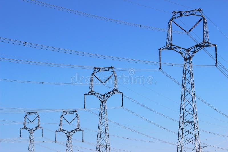 Bos van hoogspanningstorens onder blauwe hemel stock afbeeldingen