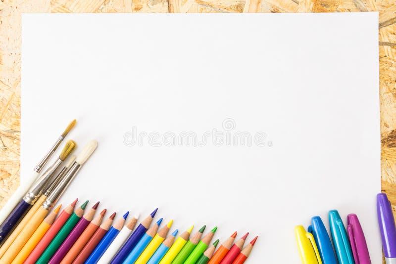 Bos van kleurrijke potloden, tellers en verfborstels, op leeg blad van document stock afbeeldingen