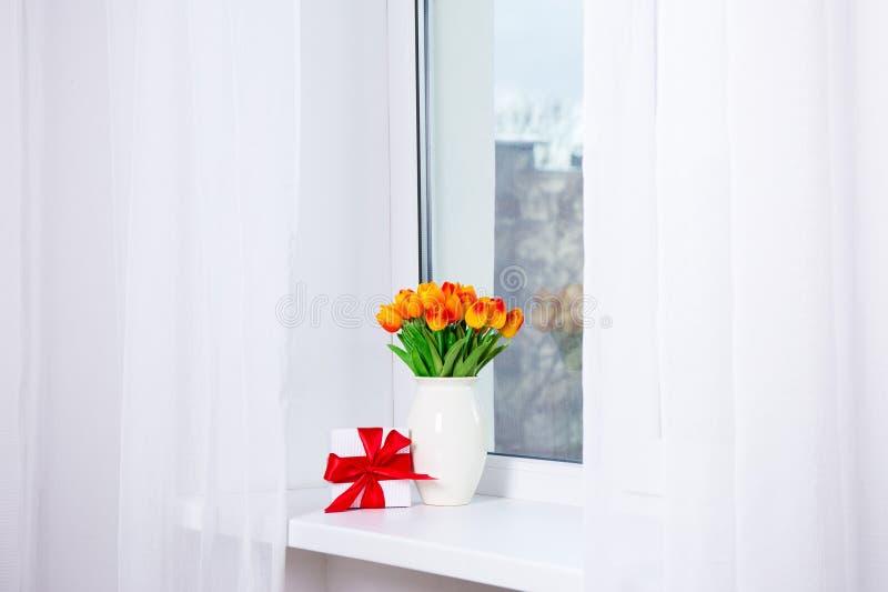 Bos van mooie tulpen en giftdoos op een venstervensterbank stock foto