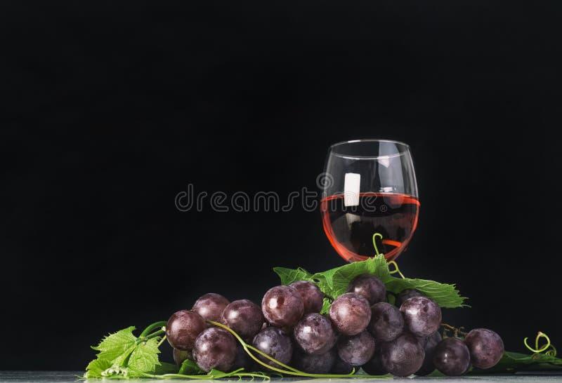 Bos van rode druiven met bladeren en rode wijnglas stock foto's
