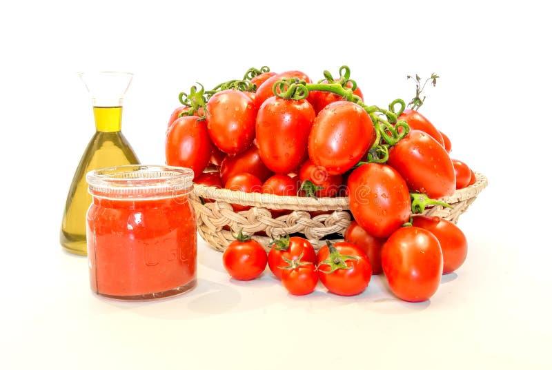 Bos van rode tomaten in een mand met olijfolie en tomatesap stock afbeeldingen