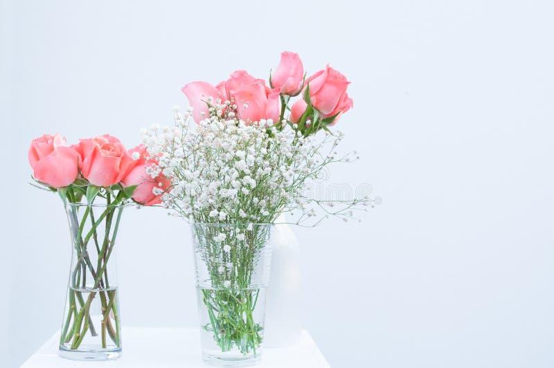 Bos van roze roze eustomabloemen in glasvaas op wit stock afbeeldingen