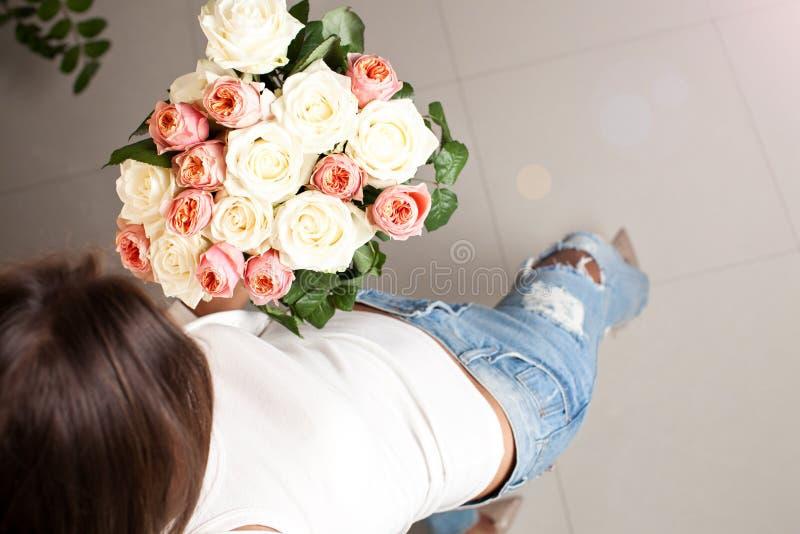 Bos van rozen in vrouwen` s handen royalty-vrije stock fotografie