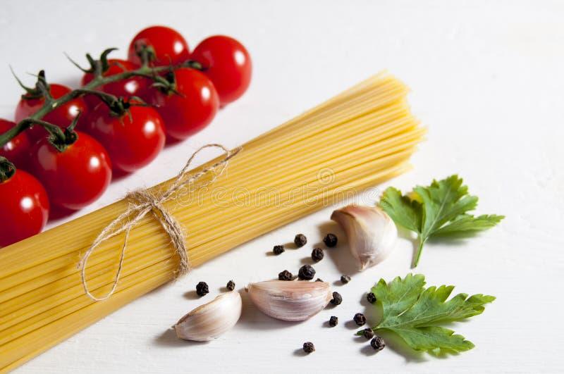 Bos van ruwe spaghetti, kersentomaten, peper, knoflookkruidnagels en peterseliebladeren op een witte houten achtergrond Close-up royalty-vrije stock afbeeldingen