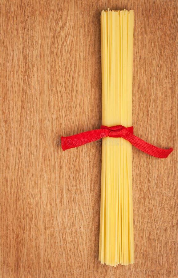 Bos van spaghetti die met een rood lint wordt verbonden stock fotografie
