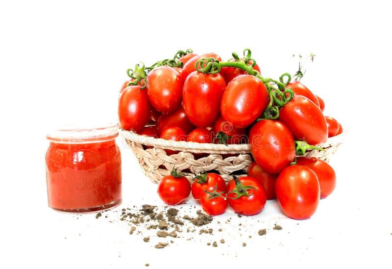 Bos van tomaten in een mand met tomatesap stock afbeeldingen