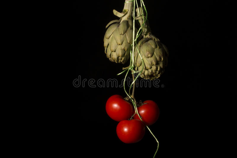 Bos van tomaten en artisjokken stock afbeeldingen