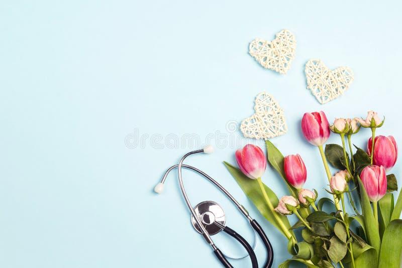 Bos van tulpen en rozen met stethoscoop op blauwe achtergrond Hoogste mening met exemplaarruimte royalty-vrije stock fotografie