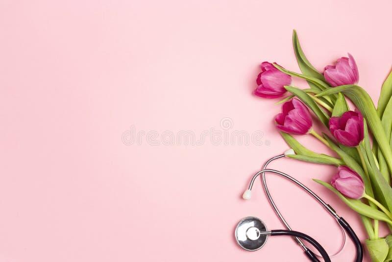 Bos van tulpen en stethoscoop op roze achtergrond De hoogste ruimte van het menings wiyh exemplaar Nationale Artsen` s dag royalty-vrije stock afbeelding