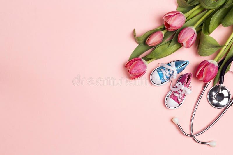 Bos van tulpen met stethoscoop en babyschoenen op roze achtergrond Hoogste mening met exemplaarruimte royalty-vrije stock afbeelding