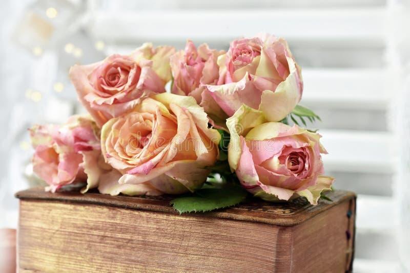 Bos van veelkleurige rozen die op oud boek liggen stock foto's