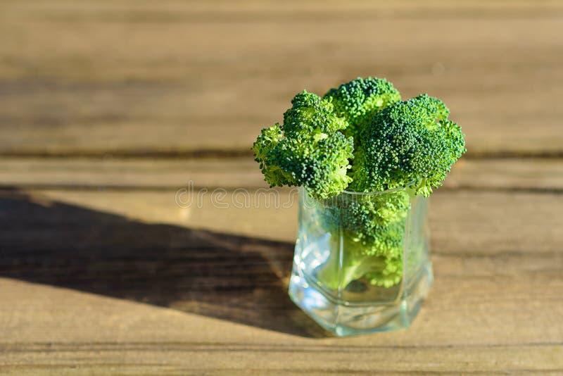 Bos van verse groene broccoli in glas op houten lijst dichte omhooggaand op de achtergrond van een steenmuur royalty-vrije stock fotografie