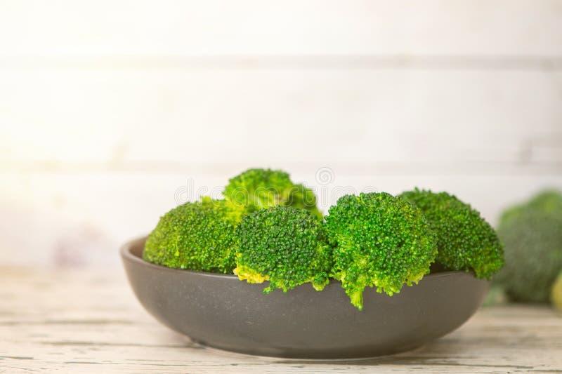 Bos van Verse groene broccoli op zwarte plaat over lichte houten achtergrond Zachte nadruk royalty-vrije stock afbeeldingen
