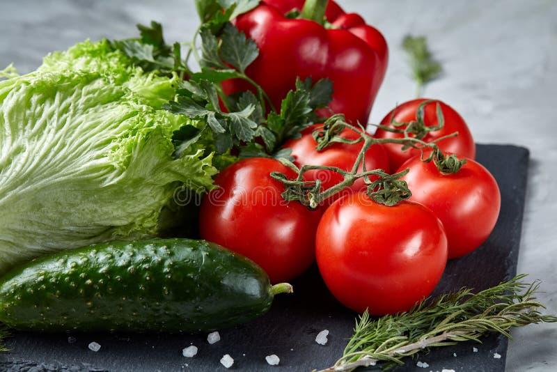 Bos van verse tomaten met groene bladeren op steenachtige raad over witte achtergrond, hoogste mening, close-up, selectieve nadru stock foto
