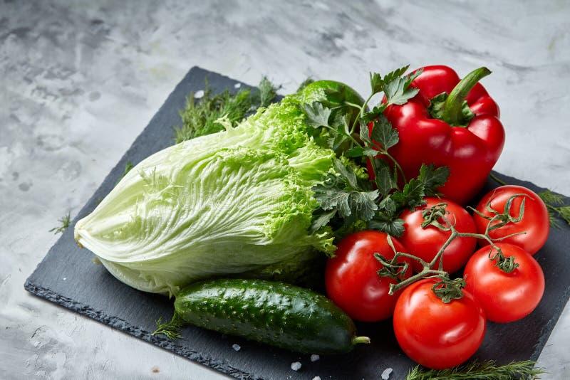 Bos van verse tomaten met groene bladeren op steenachtige raad over witte achtergrond, hoogste mening, close-up, selectieve nadru royalty-vrije stock foto's