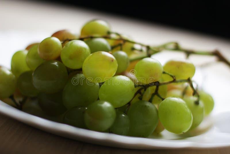 Bos van witte druiven op de witte plaat royalty-vrije stock fotografie