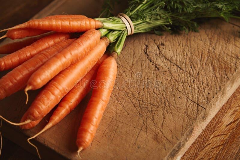 Bos van wortelen op een oude scherpe raad royalty-vrije stock foto's
