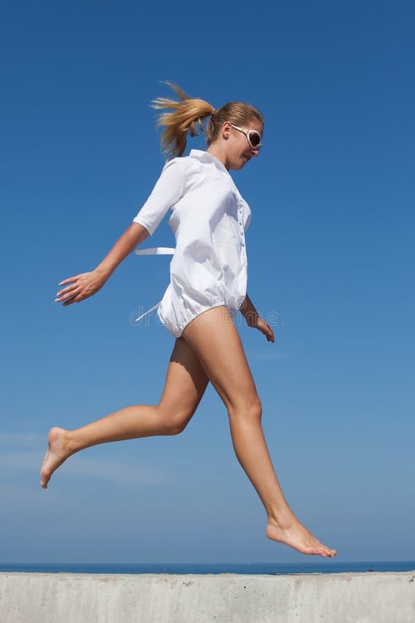 Bosa dziewczyna w bielu skr?tu sukni jogs na betonowej budowie zdjęcia royalty free