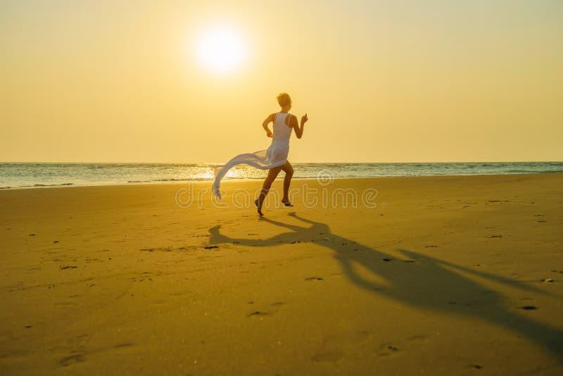 Bosa młoda kobieta w biel ubraniach biega daleko od na piasku na opustoszałej plaży przy zmierzchem nad morzem Długa spódnica trz fotografia stock