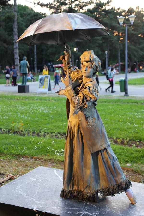 Bosatt staty - dam med paraplyet royaltyfri bild