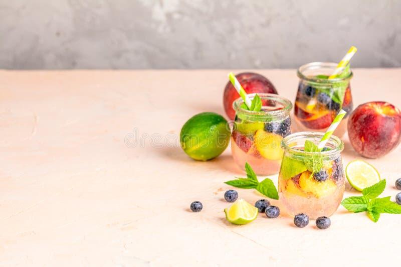 Bosbes en perzik gegoten water, cocktail, limonade of thee De zomer bevroren koude drank met bosbes, kalk, perzik en munt royalty-vrije stock afbeelding